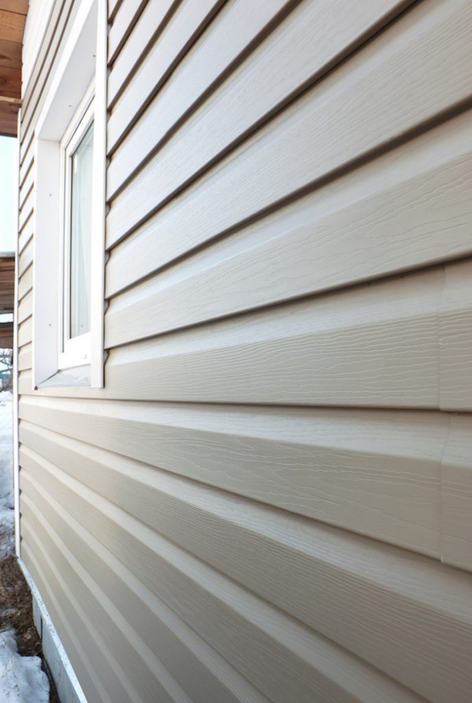 Wall of the house, finished in vinyl siding and window